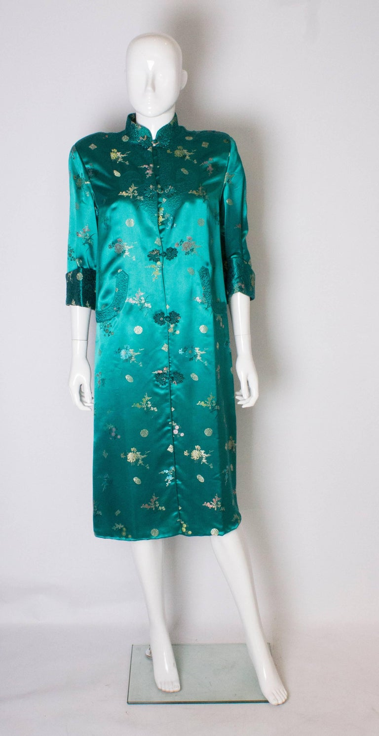 A stunning coat in a wonderful sea green colour with embroidery. The coat has a stand up collar, turn back cuffs, decorative pockets and 12'' slits on either side. it is fully lined, and will fit a bust up to 39''.