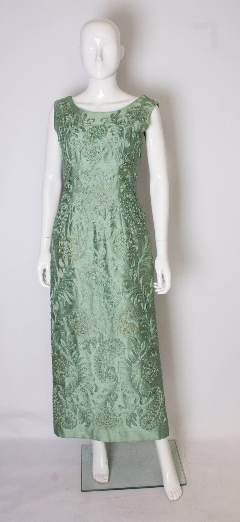 A chic sage green evening gown by Carita Couture . The dress is made of a sage green fabric, speckled with gold and has ribbon decoration. The dress has a scoop back and front with a  central back zip, and a 15'' slit at the back.