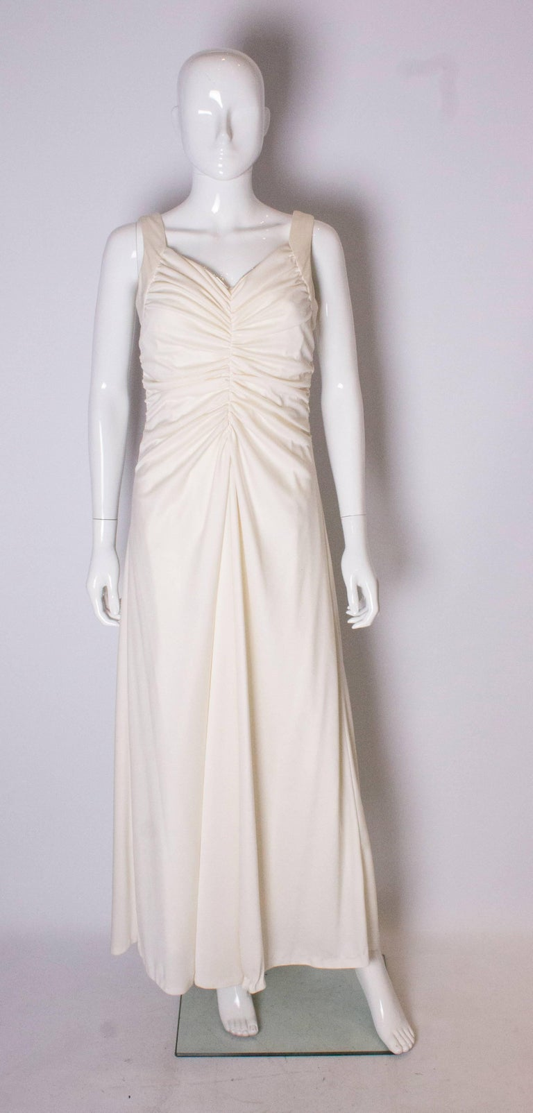 A great dress for summer in white with a silver trim.The dress has gathering at the front and back , and drapes from  below the bust. it has a central back zip , and is fully lined.