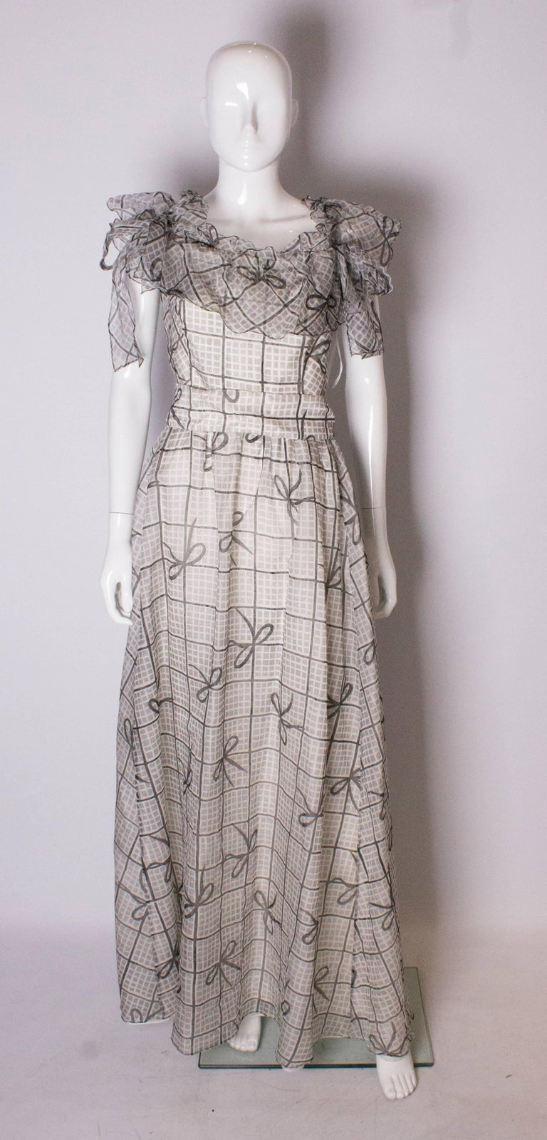 A stunning silk gown by Gina Fratini. The dress is  made of silk in a black, grey and white print, with  two layers of lining, one in organza and the other in lining fabric. The dress has boning in the bust area, and frills at the neckline with a