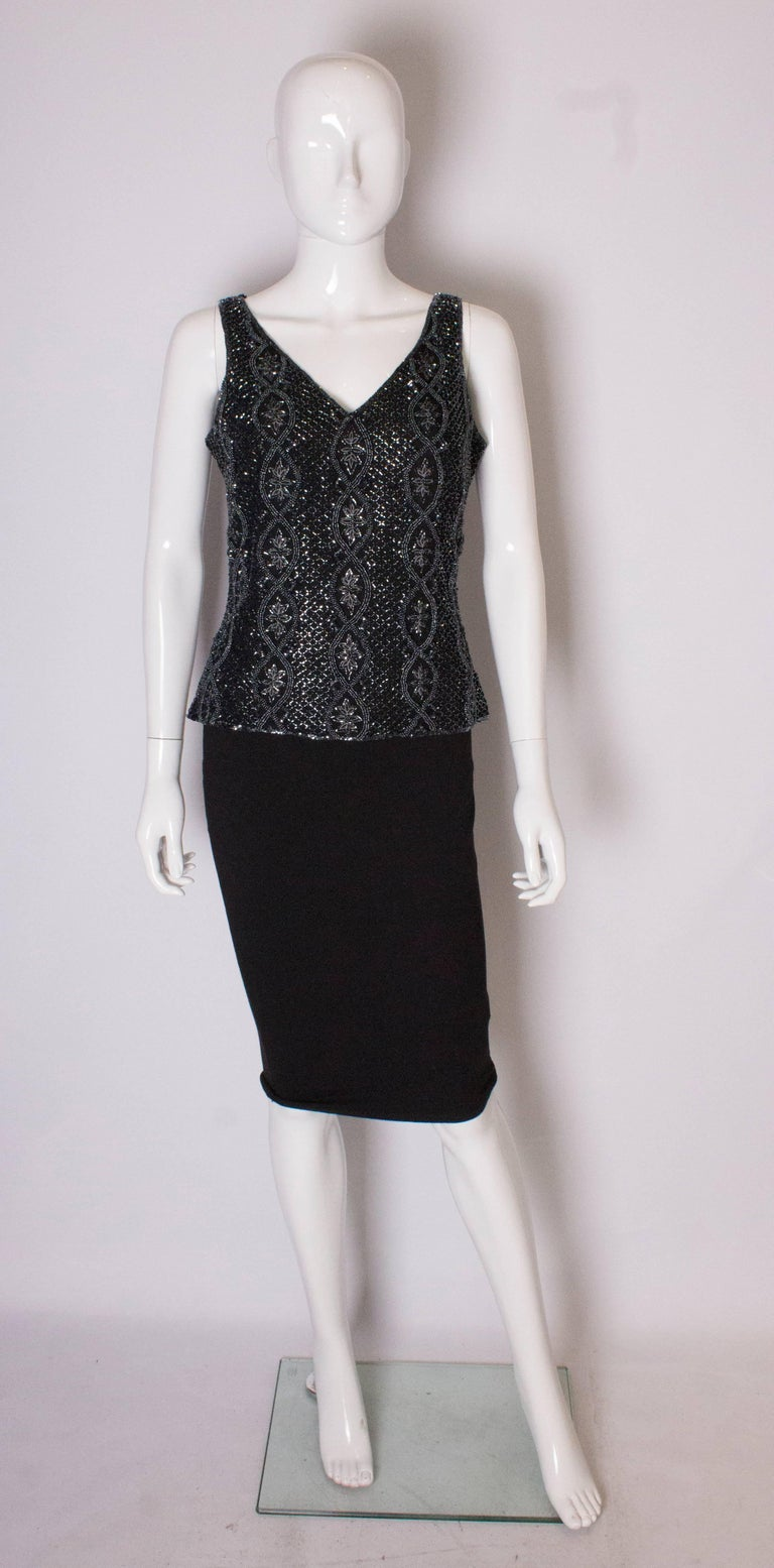 A chic evening top by Adrianna Papelle. The top has a v neckline front and back , with beading in a floral design and in vertical columns.  it has  a central back zip.
