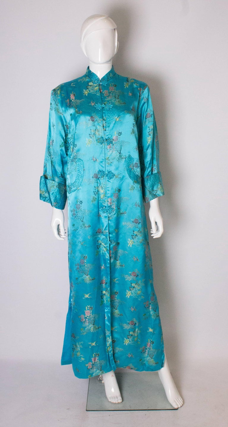 A stunning long  turquoise satin chinease coat . The coat is fully lined, has a stand up collar and  two attractive pockets at the front.  It has 17'' slits on either side, and elbow length sleaves.