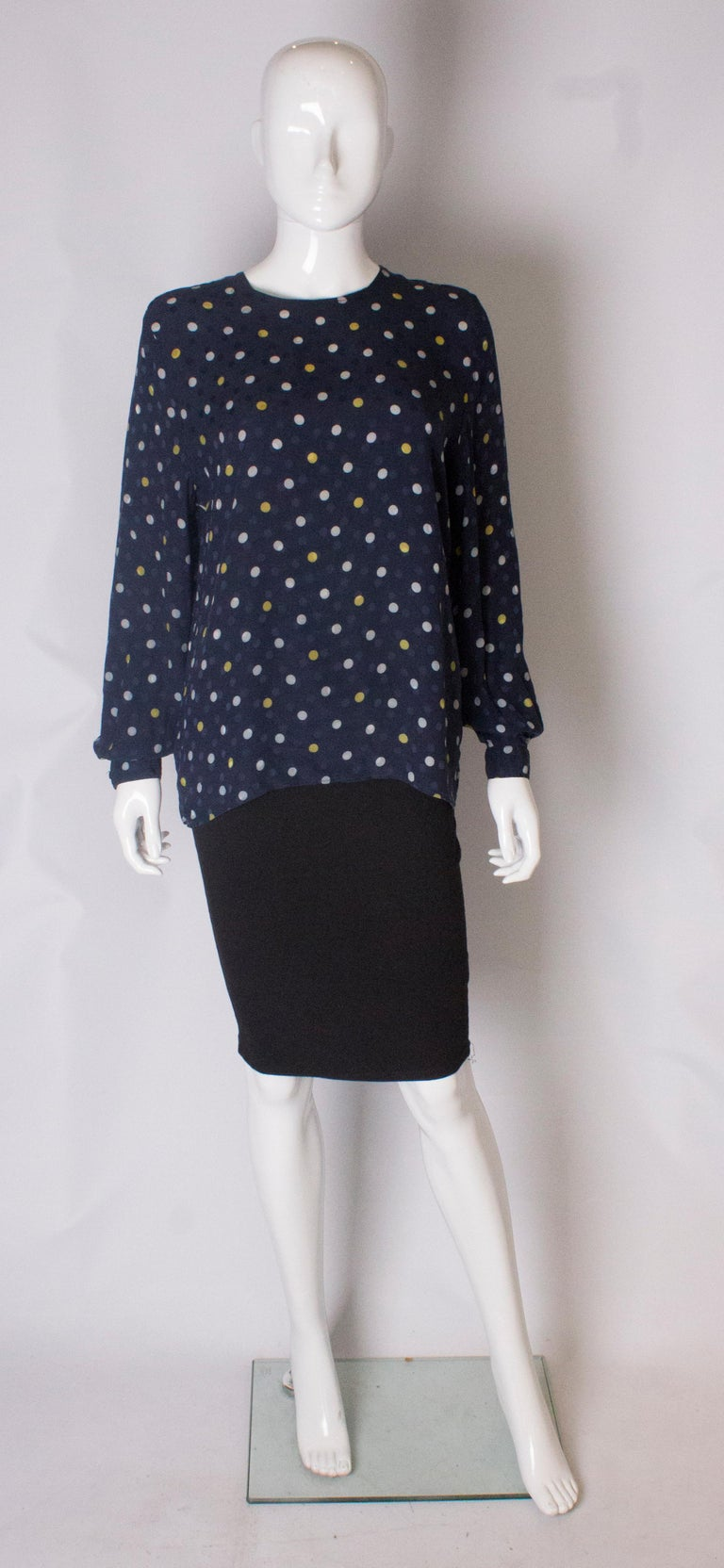 A chic silk blouse by Valentino. The blouse has long sleeves with a single button cuff, and a button opening at the back. The silk has blue dots in the background with yellow and white spots in the foreground.