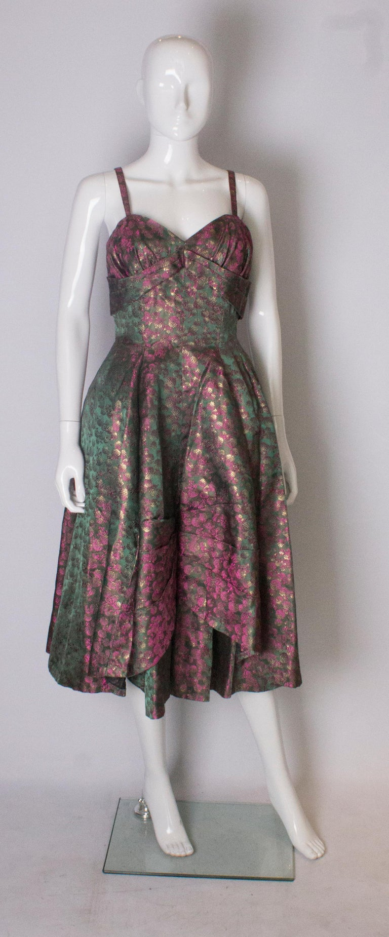 A chic cocktail dress in a pink and green brocade  combination.  The upper part is boned, with a fold under the bust and the skirt has a built in petticoat. The dress has a central back zip.