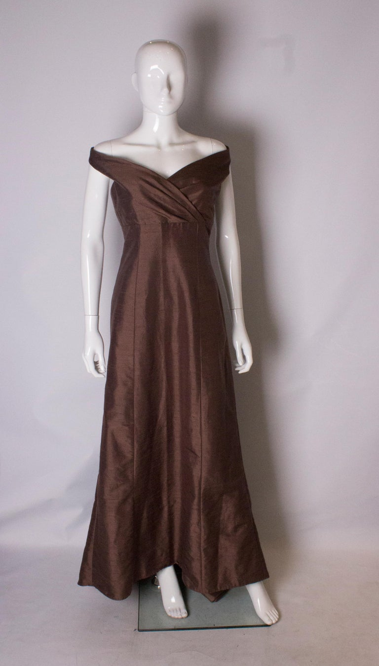 A stunning vintage silk gown in a pretty shade of brown. The dress has a cross over front , and is slightly off the shoulder. It has a central back zip, is fully lined, and has a puddle train.