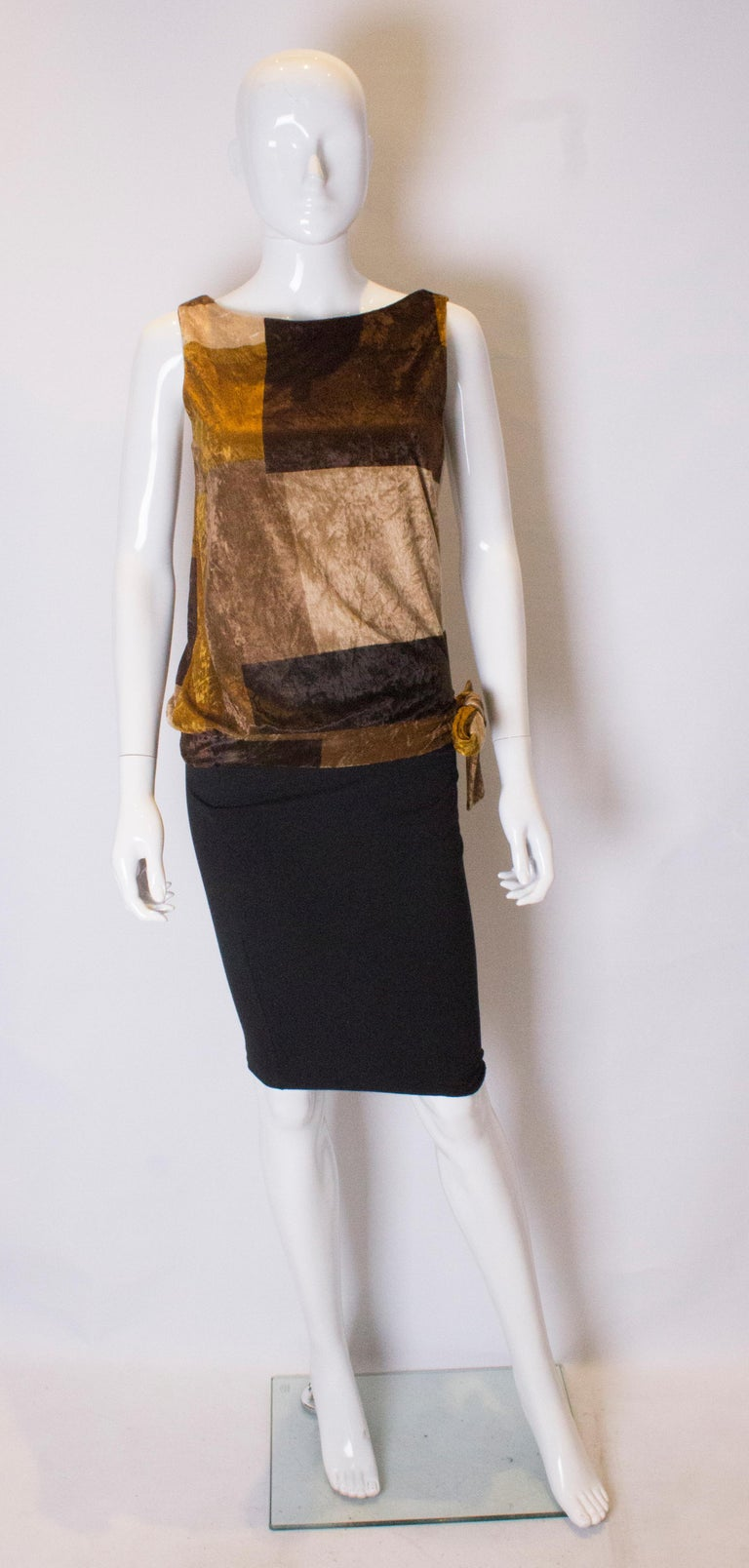 A great top for fall.  In a lovely light velvet , the top is in various shades  of gold and brown. It is sleaveless and ties at the waist on one side.