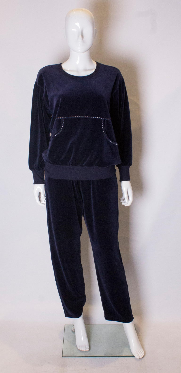 A super stylish leisure suit by Sonia Rykiel. The suit is in a deep blue velour , with two pouch pockets at the front. The top has a scoop round neck and diamante detail at the front and back. The trousers have an elasticated waist and two pockets