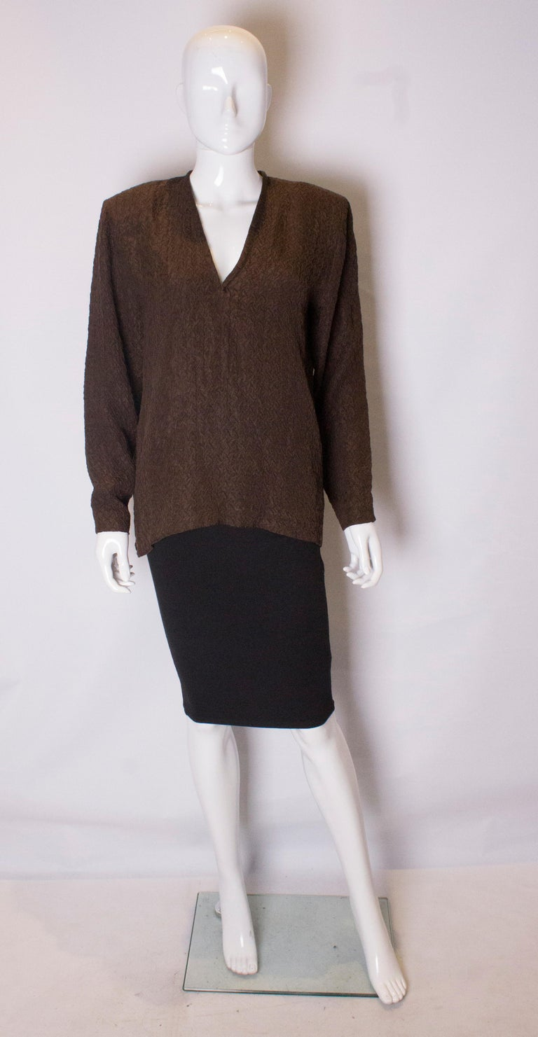 A great silk blouse by Yves Saint Laurent rive Gauche line . In a brown textured crinkle silk, the blouse has a v neckline and small shoulder pads.