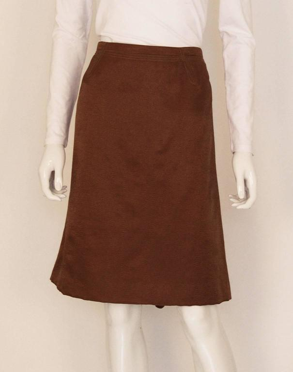 A wonderful bronze coloured skirt by Nina Ricci, Paris. The skirt is made of a luxurious wool mix, and is fully lined. There is a double row of stitching on the waist band , and the back has an interesting zig zag detail and gathering.