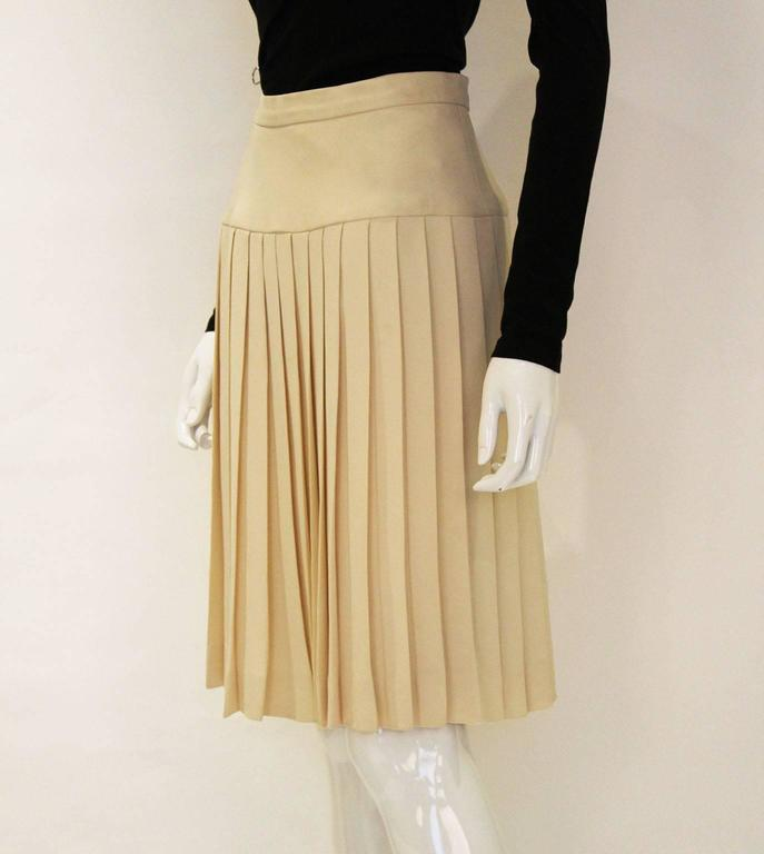 A wonderful silk skirt by Chanel .This skirt is in a lovely pale cream colour. The skirt fabric is a very heavy silk ( the pleats hang beautifully ) and the lining is silk with the Chanel logo worked into the fabric. The pleats start at hip level,