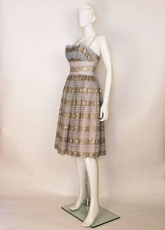 A chic cocktail/evening dress by Victor Josselyn. In a pale blue fabric with gold and silver decoration, plus white horizontal braiding, this dress is a great party piece. It has spaghetti straps,  a full skirt and is fully lined.