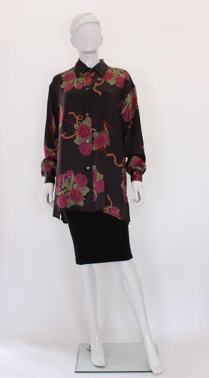 A great silk overshirt by Salvatore Ferragamo.This shirt is in a beautiful silk, with a brown background and pink floral print.The shirt has a one button cuff, and 5 button opening at the front.All the buttons are stamped Ferragamo, and the shirt
