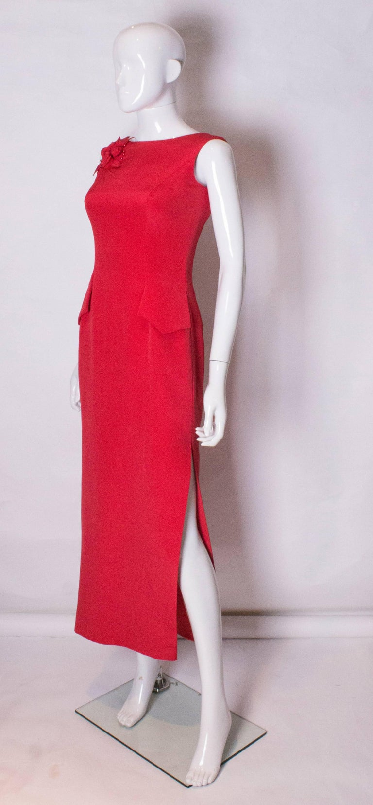 A stunning evening gown by British designer Tomasz Starzewski,  The dress has a slash neckline at the front and a deep v neckline at the back with a central back zip.It has a red floral and bead decoration on the right shoulder, a slit on the left