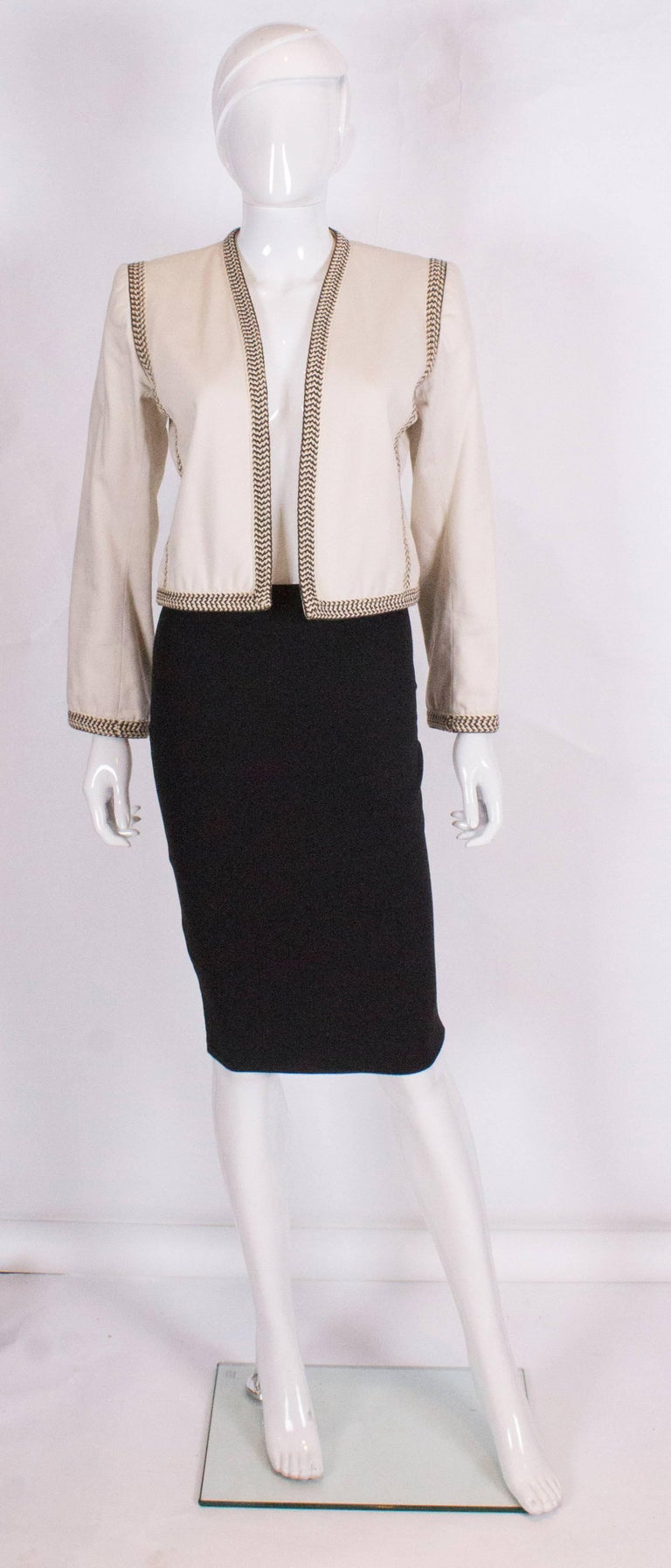 A chic jacket by Yves Saint Laurent Rive Gauche . The jacket is lined in cotton and has a braid trim at the neckline, cuffs and down the front and back.It has the original shoulder pads.