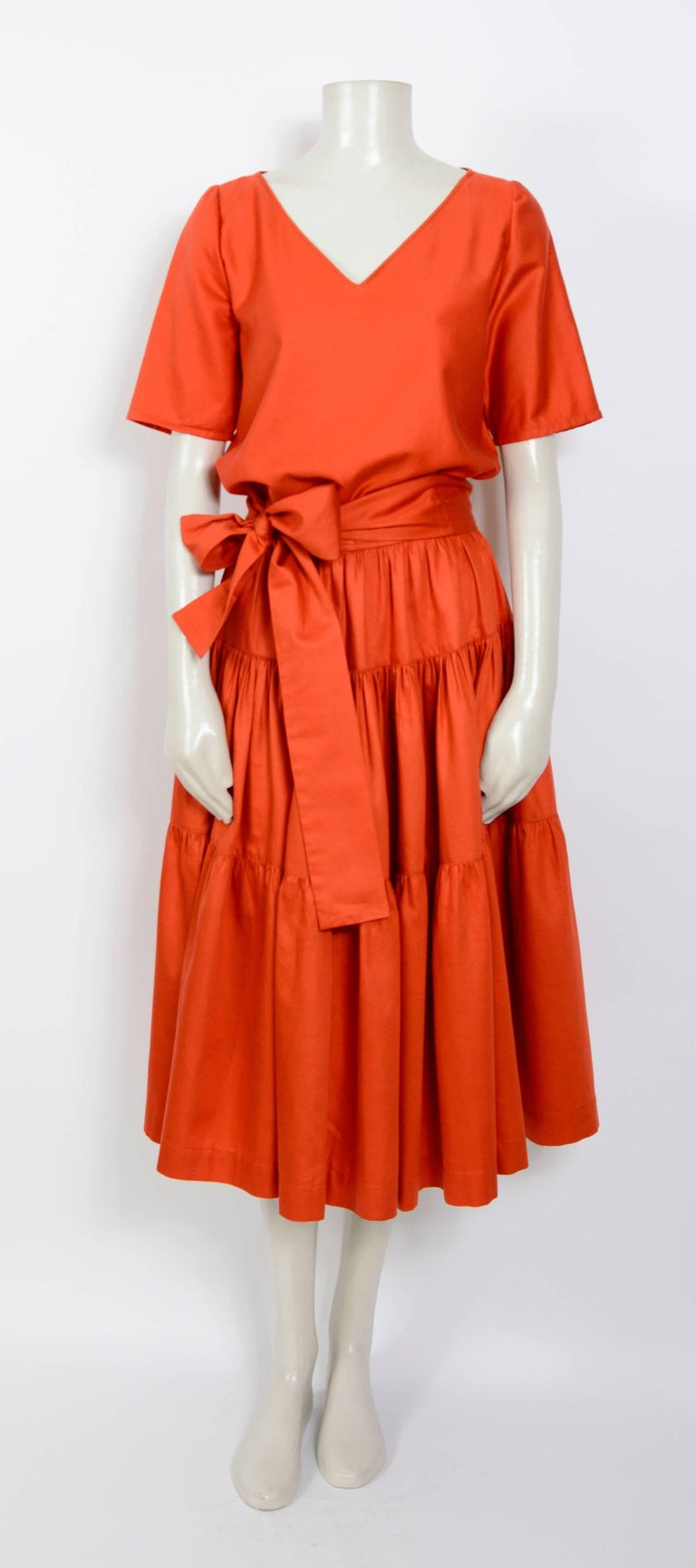A fabulous 1960's top and skirt from YSL Rive Gauche in Redstone red polished cotton. The skirt has a fitted waistband, 3 gathered panels each widening towards the hem making it fuller and a wide tie belt. The top slips on over the head and the