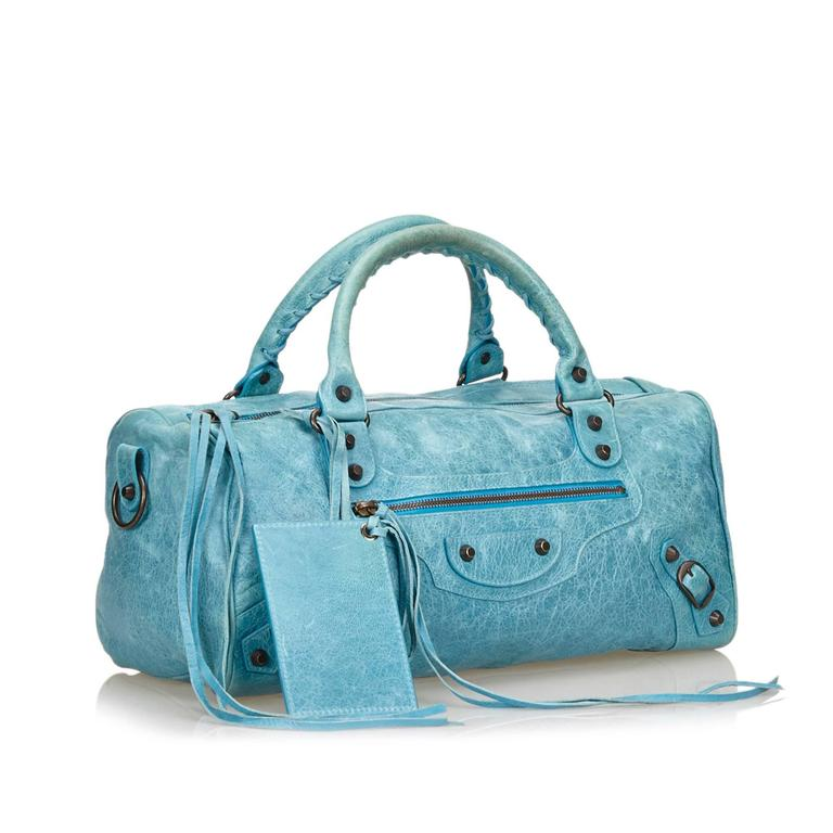 The Motocross Twiggy features a leather body with strap and tassel details, silver-tone hardware, a top zip closure, and an interior zip pocket. It comes with a shoulder strap and a mirror.  Color: Blue