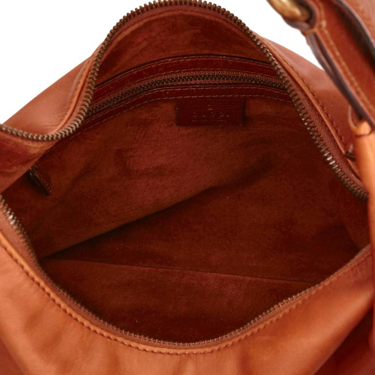 This shoulder bag features a coated canvas body, a flat shoulder strap with horse bit details, a top zip closure, and an interior zip pocket.