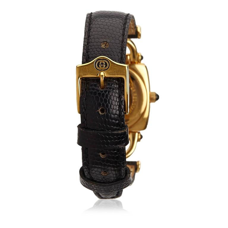 This watch features a gold-tone face, an embossed leather strap, a buckle closure, and a quartz movement.