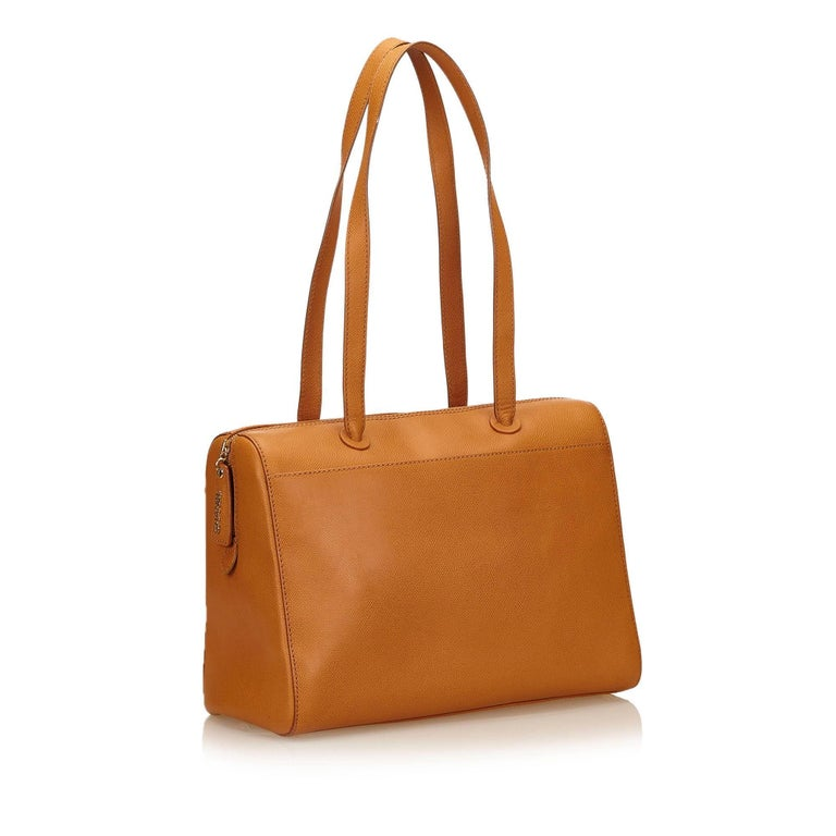 This shoulder bag features a leather body, flat leather straps, top zip closure, and interior zip pocket.  It carries a B condition rating.  Dimensions:  Length 35 cm Width 25 cm Depth 15 cm Shoulder Drop 31cm  Inclusions: Dust Bag  Color: