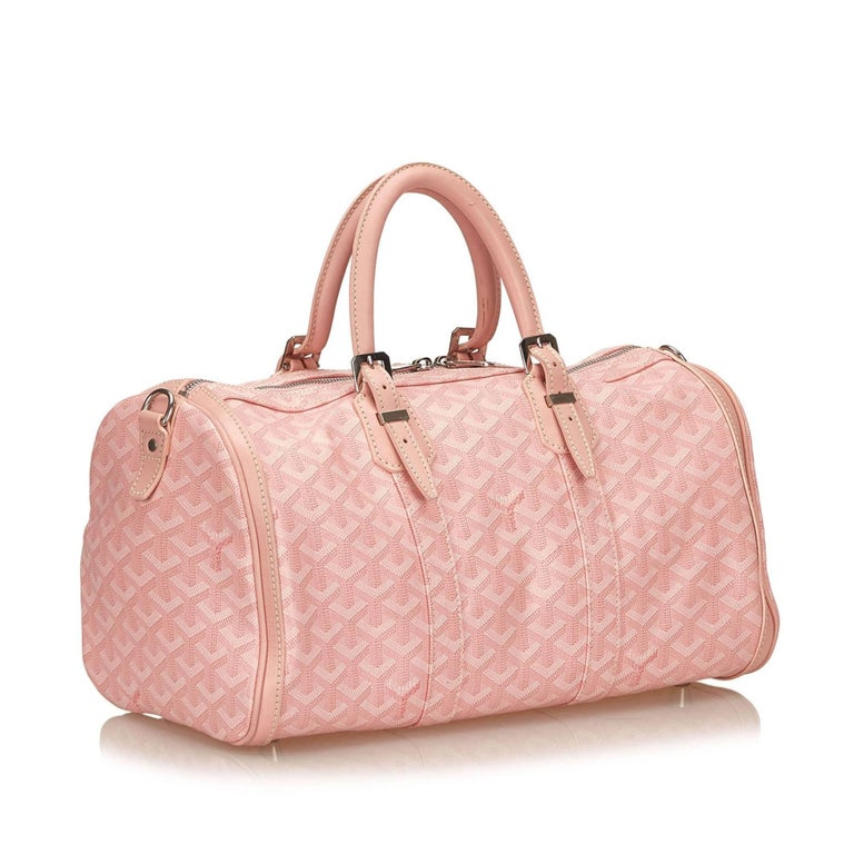 The Goyardine Croisiere 35 features a coated canvas body, rolled leather  handles, and a 042356d559