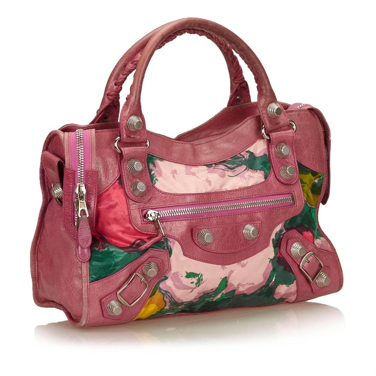 The Motocross Floral Giant 12 City features a print on a fabric body with leather trim, rolled handles, an exterior zip pocket, a top zip closure, and an interior zip pocket.   It carries a B condition rating.  Dimensions:   Length 26 cm Width 37