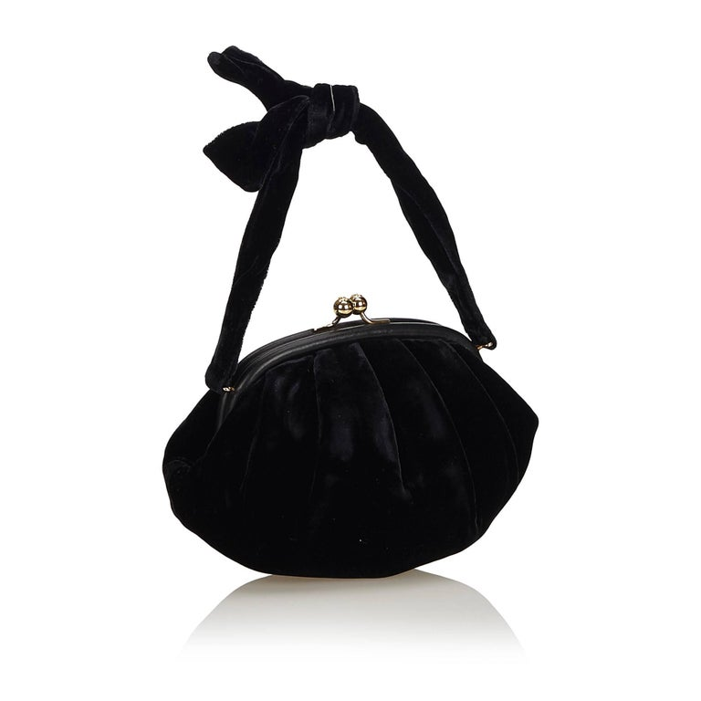 This handbag features a velour body, knotted strap, kiss lock closure, and interior slip pocket.   It carries an AB condition rating.  Dimensions:  Length 22 cm Width 16 cm Depth 10 cm Hand Drop 10cm  Inclusions: Dust Bag  Color: Black  Material: