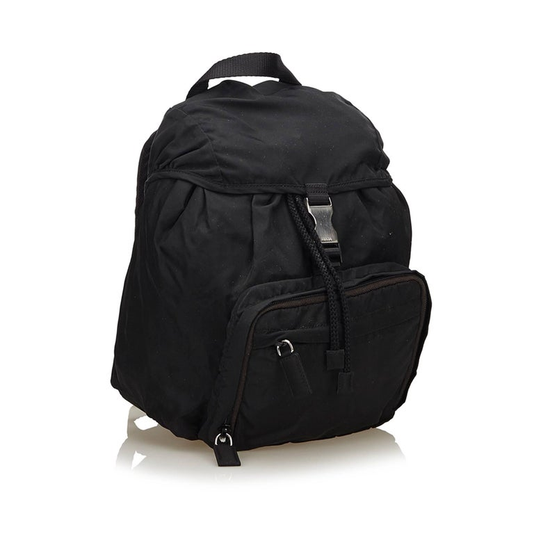 This backpack features a nylon body, flat back straps, flat top handle, a top flap with a buckle closure, a top drawstring closure, and exterior zip pockets.   It carries a B+ condition rating.  Dimensions:  Length 25 cm Width 23 cm Depth 12