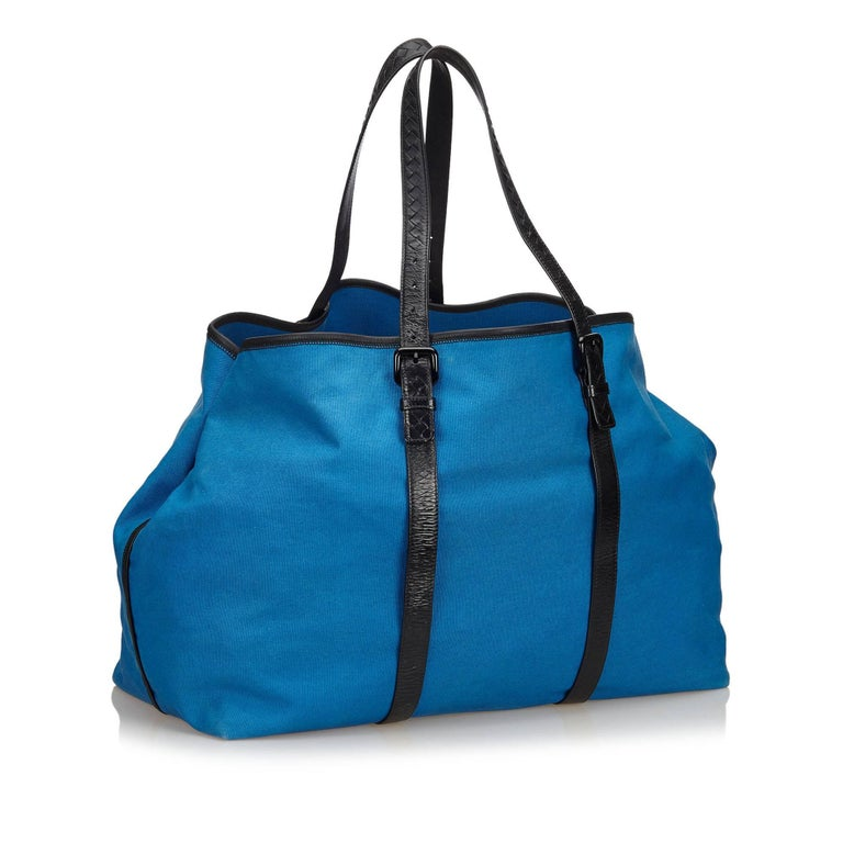This weekender features a canvas body with leather trim, flat leather straps, and an open top.   It carries an AB condition rating.  Dimensions:  Length 28 cm Width 54 cm Depth 25 cm Shoulder Drop 25 cm  Inclusions: No longer comes with original