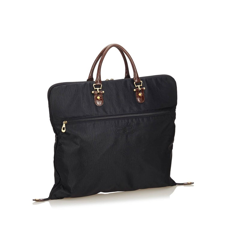 91c8fb654a This garment bag features a nylon body, rolled leather handles, exterior  back zip pocket