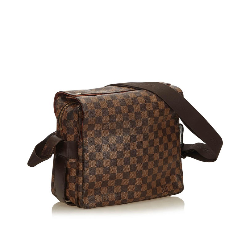 The Naviglio features a damier ebene canvas body, flat strap, top flap with snap closure, top zip closure, and an interior slip pocket.  It carries a B condition rating.  Dimensions:  Length 24.00 cm Width 28.00 cm Depth 14.00 cm Shoulder Drop 56.00