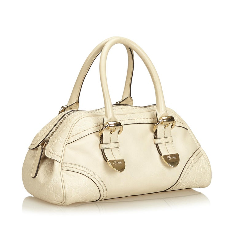 This shoulder bag features a leather body, rolled leather handles, top zip closure, interior slip pocket, and an interior zip pocket.  It carries a AB condition rating.  Dimensions:  Length 22.00 cm Width 35.50 cm Depth 10.00 cm Shoulder Drop 9.00
