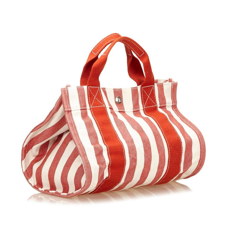 The Cannes PM tote bag features a canvas body and a top clasp closure. It carries a B condition rating.  Inclusions:  Pouch