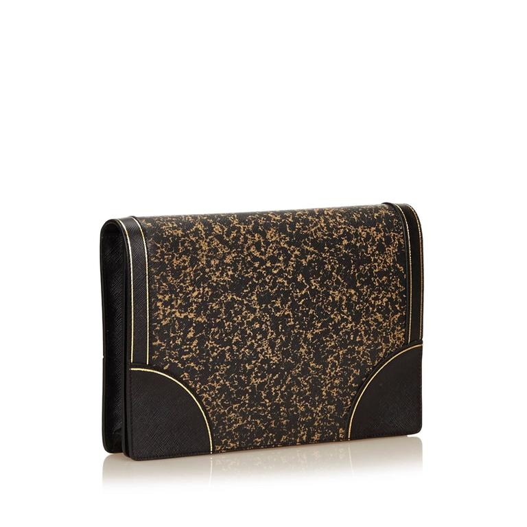 This clutch features a leather body, a front flap with a stud closure, and an interior zip pocket. It carries a AB condition rating.  Inclusions:  Dust Bag Authenticity Card ShoulderStrap