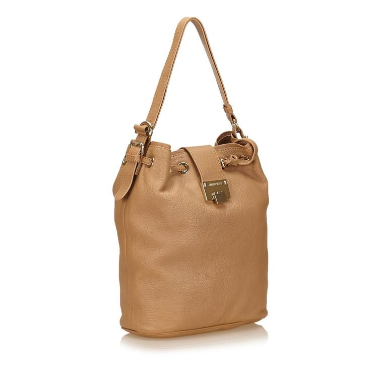 This shoulder bag features a leather body, a flat shoulder strap, a top drawstring closure, and an interior zip pocket. It carries a B+ condition rating.  Inclusions:  This item does not come with inclusions.