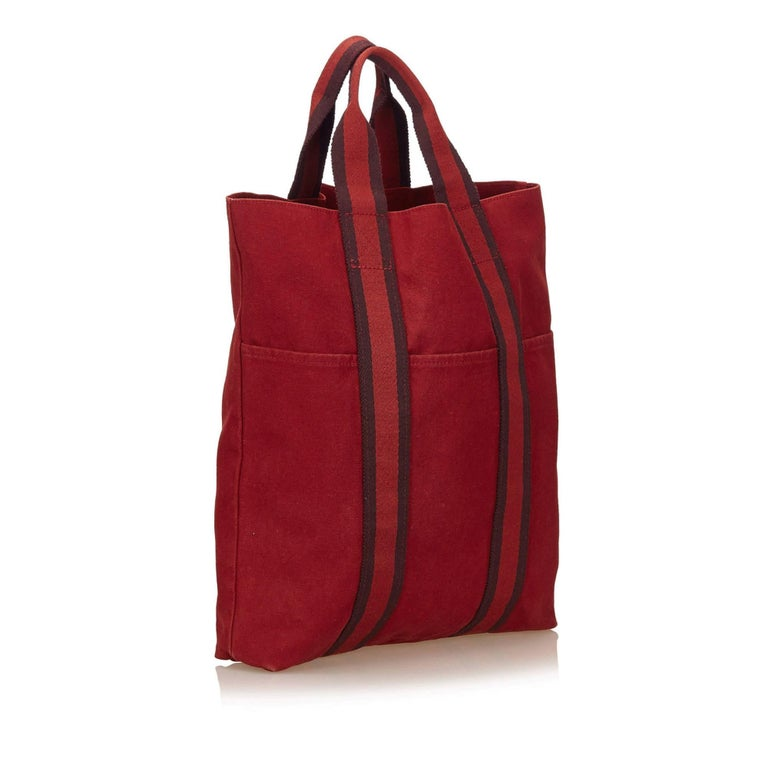 The Fourre Tout Cabas tote features a canvas body, exterior slip pockets, an open top, and an interior slip pocket. The edges of the bag are slightly worn and the material is slightly discolored.