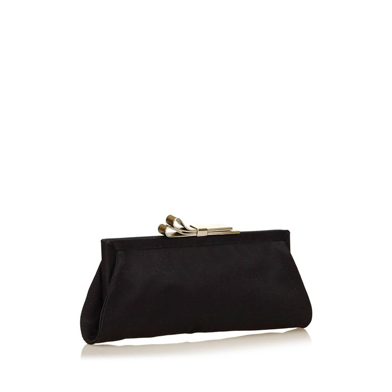 This clutch features a nylon body, a metal frame, and a kiss lock closure.