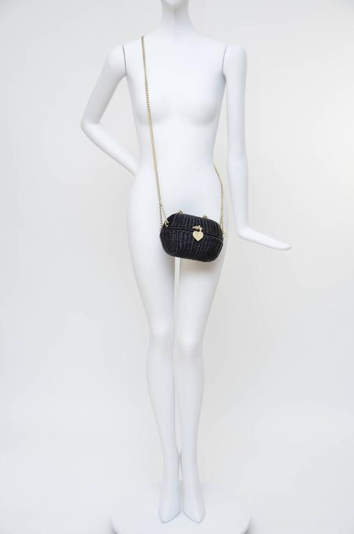 Excellent like new Chanel black mini straw handbag. This Highly Collectible Authentic Chanel Sweetheart  black handbag was designed in 2005.it is called the Divers Sac. It is a straw woven wicker basket with a heart shaped closure. All the hardware