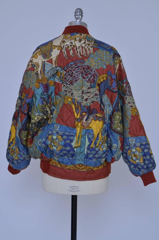 Hermes silk vintage bomber jacket. Burgundy,  gold and multicolor silk Hermès reversible printed quilted jacket with rib knit trim throughout, four slit pockets at sides and concealed zip closure at center front. Condition: Looks new