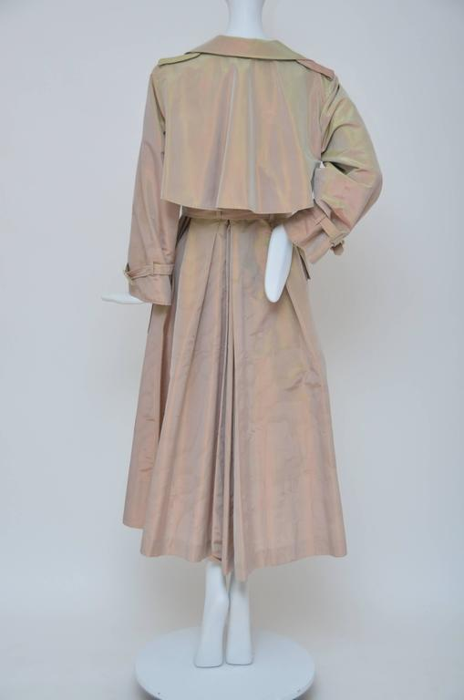 Givenchy Haute Couture iridescence fabric trench coat. Very good condition.Fabric is nice and clean. One button missing in the front.Belt buckle has minor split but it can be glued. 2 large X 2 small pockets in the front. Fabric is just amazing