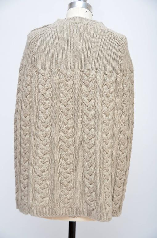 Beige Louis Vuitton wool poncho with cable knit throughout. Crew neck, arm slits with LV button closure at sides and 3 metal LV button closures at left shoulder.  Condition is like new,look's unworn. Size M.Could fit multiple sizes....depends how