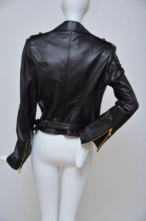 Versace black Leather Biker Jacket. Black leather epaulettes, studded lapels, zipped cuffs, two zipped front pockets, front flap pocket, fully lined exposed asymmetric zip fastening through front 100% leather (lamb); lining: 96% rayon, 4% elastane