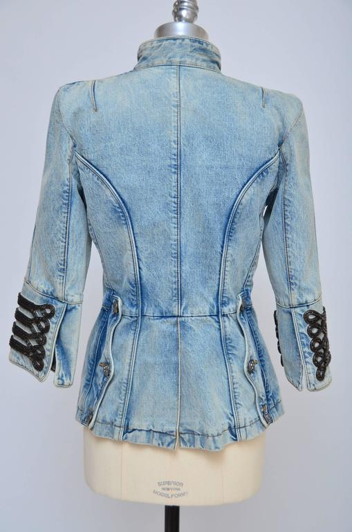 Double breasted denim jacket with military detail. Jacket has three-quarter length sleeves, padded shoulders, is unlined and fastens on front with buttons at side. 100% cotton. Dry clean. 