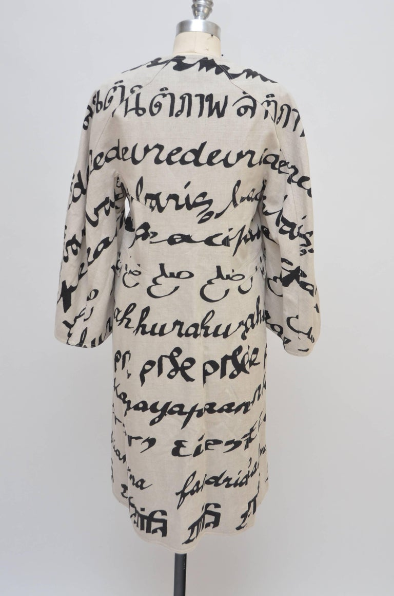 Creme and black Ralph Rucci collarless linen coat with abstract print throughout, three-quarter sleeves and button closures at front. Bust: 37