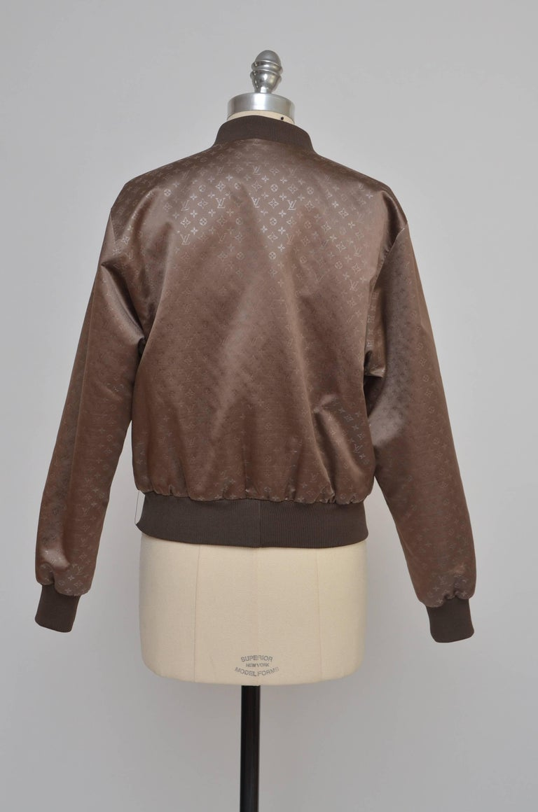 Louis Vuitton silk monogram jacket  with dual welt pockets at sides, rib knit trim and button clasp  snap closures at center front. Size 38 FR. New condition without tags. Approximate measure:Bust: 40