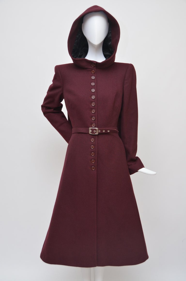 Alexander McQueen burgundy coat with hood. Exact coat as seen at  this runway  1998 collection. Coat has belt opening on the side and comes with original belt. Lined in black Alexander McQueen signature print fabric. Button closure . Excellent mint