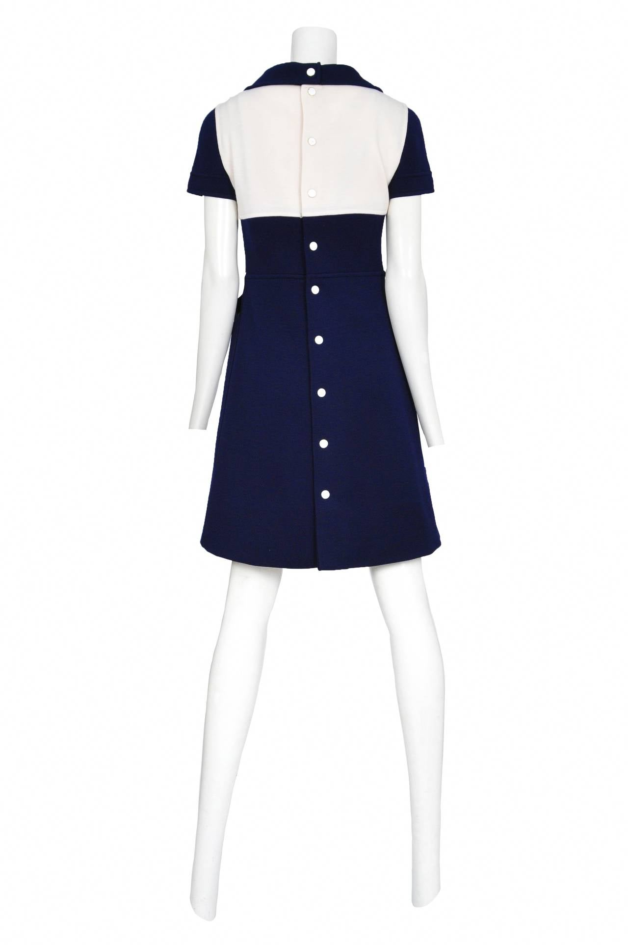 Vintage Andre Courreges blue short sleeve wool dress with white yoke featuring the Courreges symbol at neckline and white buttons up the front of the skirt as well as along the center back of the dress.