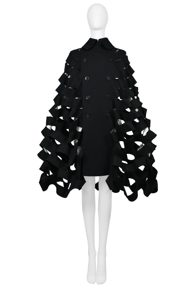 Future vintage Junya Watanabe black double breasted laser cut accordion style cape with collar. Coat features black buttons, high collar with hook and eye closure, and tailored yoke. Collection 2015.