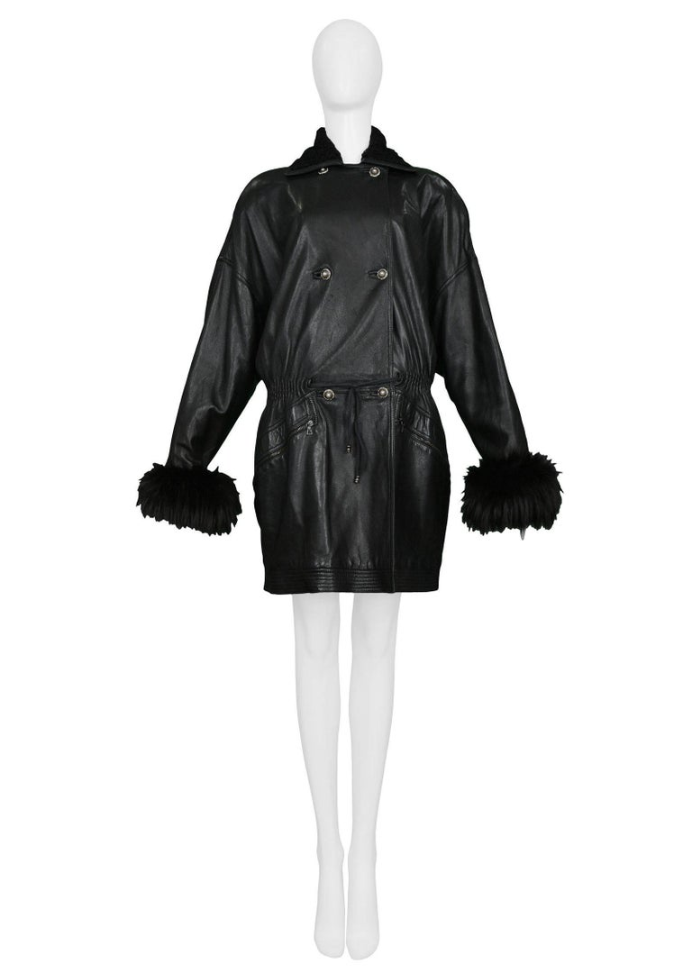 Vintage Gianni Versace black leather parka style coat with black fur cuffs and collar. The coat has a drawstring front waist, elastic back waist, soft shoulders, and decorative rhinestone buttons. Zipper pockets in front sides and quilted hem. Easy