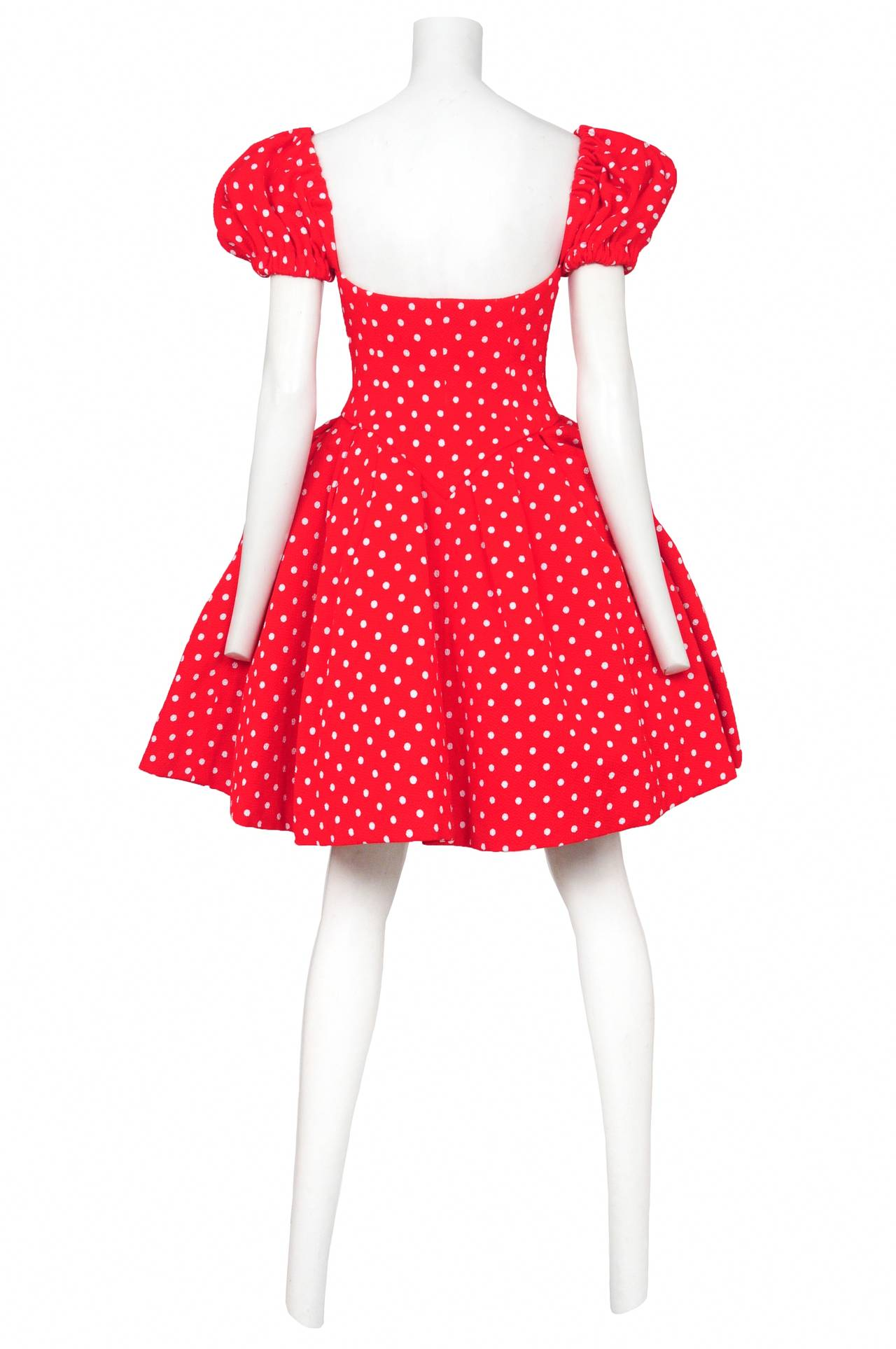 Vintage Christian Lacroix cotton blend cocktail dress featuring a red and white polka dot print, zippered front, puff sleeves, full skirt, inner corseted waist and two black grosgrain bows adorning the bust.