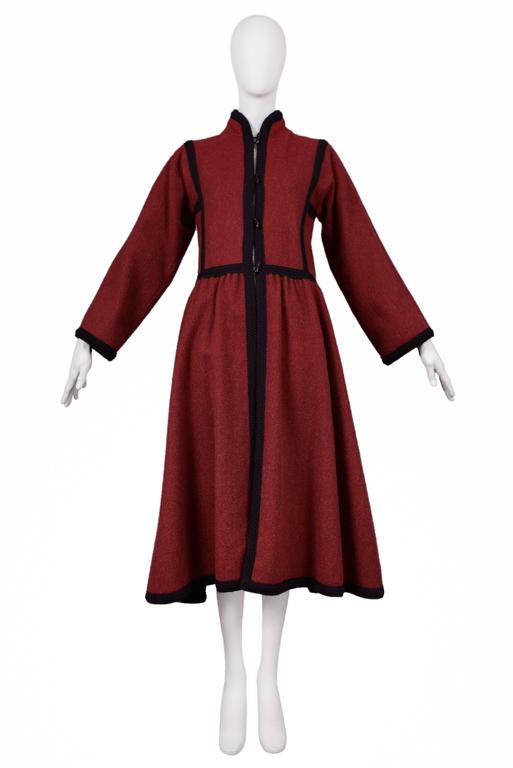 Vintage Yves Saint Laurent iconic Russian red wool coat featuring four toggles at the center front, black braided trim along the edges, and a mandarin style collar.